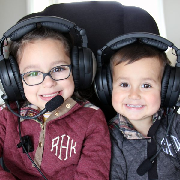 Two toddler in aviation headsets