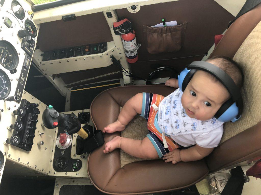 baby wearing baby manz ear muffs in an aircraft