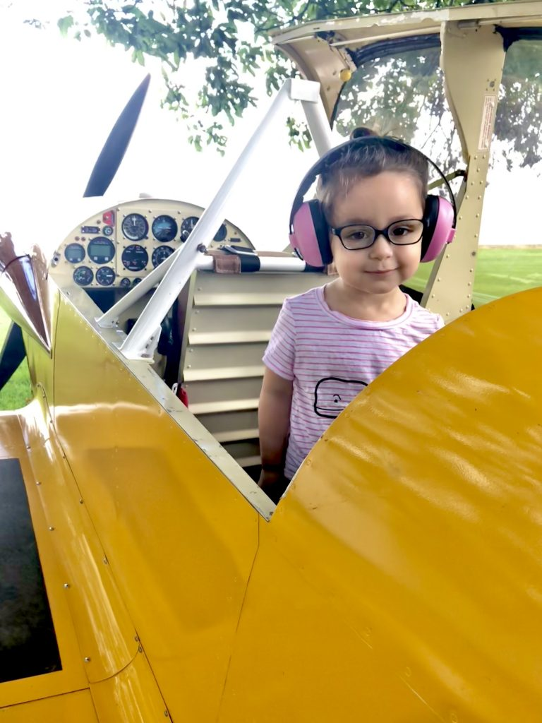 A toddler sits in an airplane wearing hearing protection.