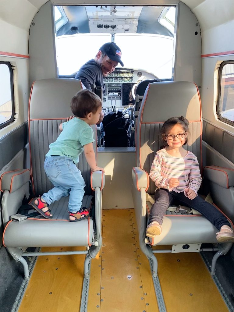 Two children sit in an airplane with their dad at the controls.