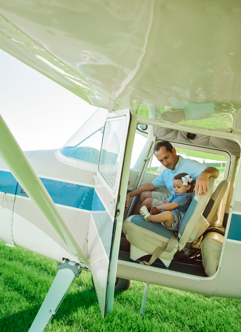 A dad sitting with his daughter in their Cessna 170.